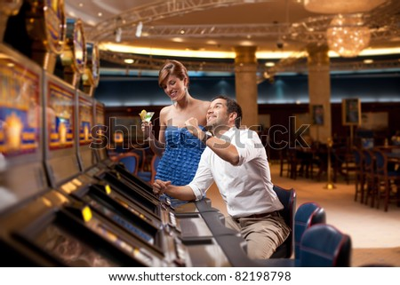 man playing slot machine, girlfriend watching smiling - stock photo