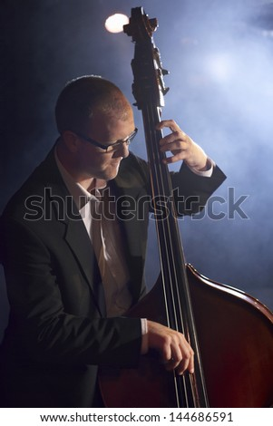 Man playing the double bass on stage - stock photo