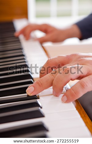 Man playing the piano with a close up view of his hands on the open keyboard as he stretches for a note - stock photo