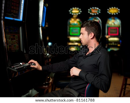 man playing the slot machin, watching carefuly - stock photo