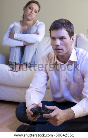 Man playing videogames, woman disappointed and bored - stock photo
