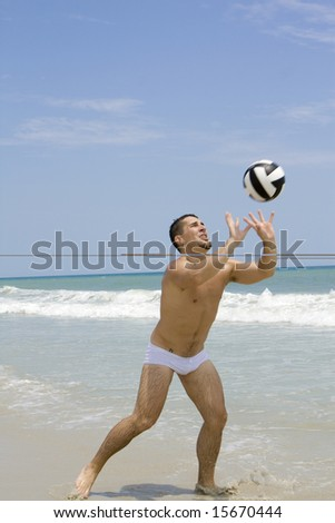 Man playing volleyball at the beach - stock photo