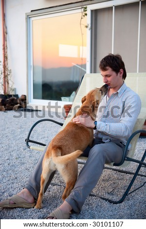 man playing with his dog in front of the house - stock photo