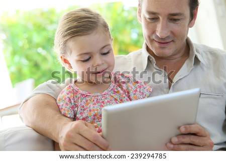 Man playing with little girl on digital tablet