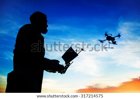 man playing with the drone. silhouette against the sunset sky - stock photo