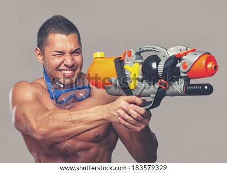 man playing with water guns in studio - stock photo