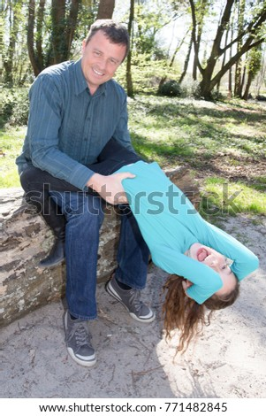 man plays in the park with his daughter dispelled