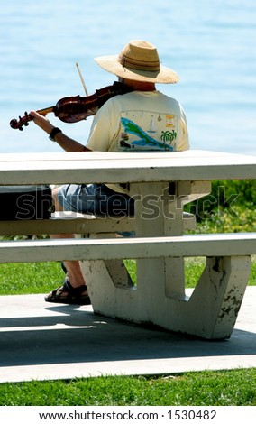 Man plays violin by the ocean. - stock photo