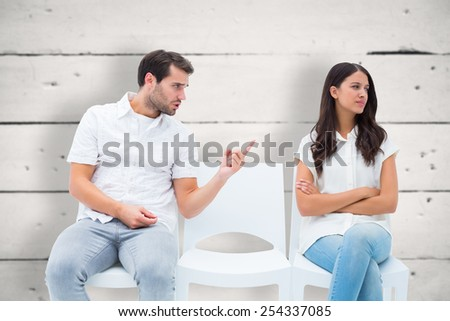Man pleading with angry girlfriend against white wood - stock photo