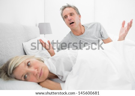 Man pleading with his upset partner in bed at home in bedroom