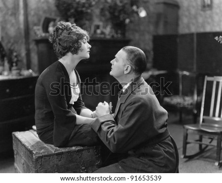 Man pleading with unwilling woman - stock photo