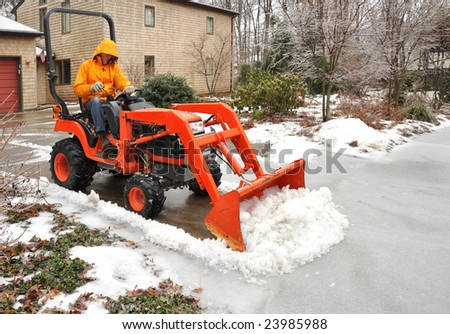 Man plowing snow and ice from a suburban driveway - stock photo