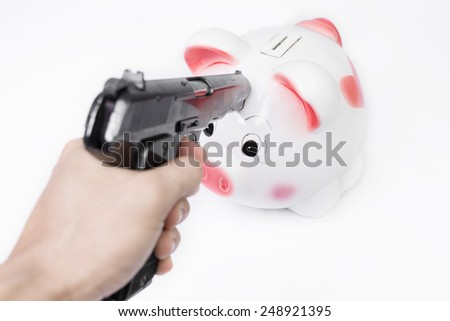 Man pointing a gun at a piggy bank no white background. - stock photo