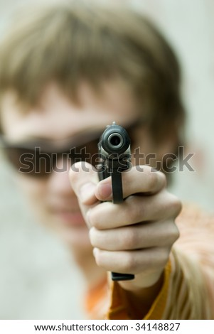 Man pointing a hand gun right at the viewer. Shallow depth of field used with focus on the barrel.