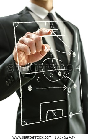 Man pointing at football field on a virtual screen to explain game strategy. - stock photo