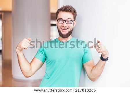 man pointing at his t-shirt (can be used as a clothes design template) - stock photo