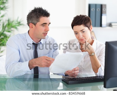Man pointing at something to his colleague on a document in an office