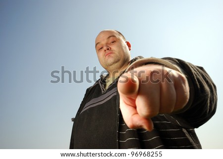 man pointing at you in front of blue sky - stock photo