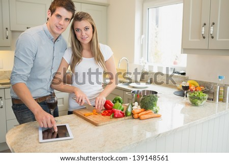 Man pointing on tablet pc wtih woman choppping peppers in kitchen - stock photo