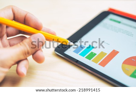 Man pointing out a colorful bar graph on a tablet - stock photo