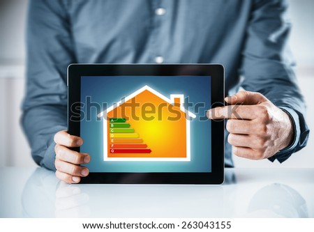 Man pointing to an online energy efficiency rating chart for a house displayed on the screen of a tablet computer, close up of his hands - stock photo