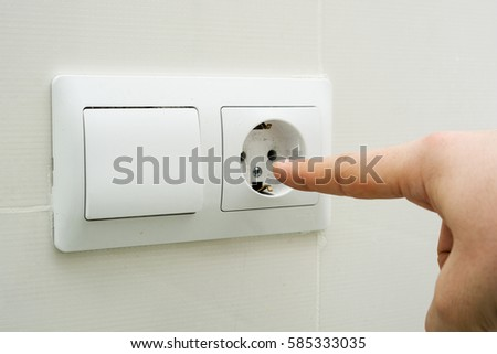 Man pokes his finger to the socket