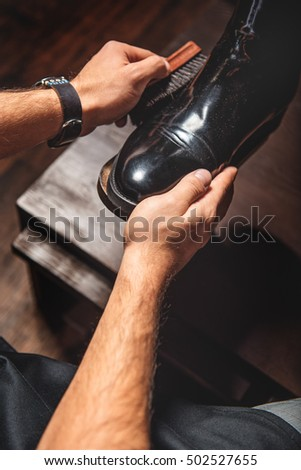 man polishing a leather pair of brogues