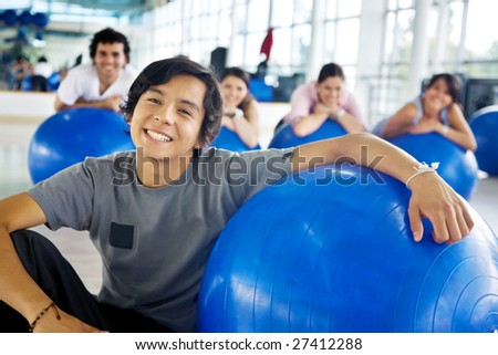 man portrait at the gym smiling with  a pilates ball