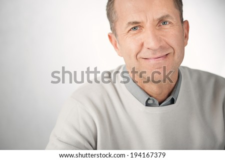 Man portrait. Good looking casual businessman on gray background. Male Caucasian model smiling. - stock photo