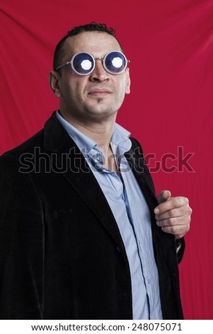 Man portrait wearing sunglasses on red background - stock photo