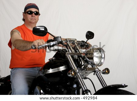 Man posed with a motorcycle. - stock photo
