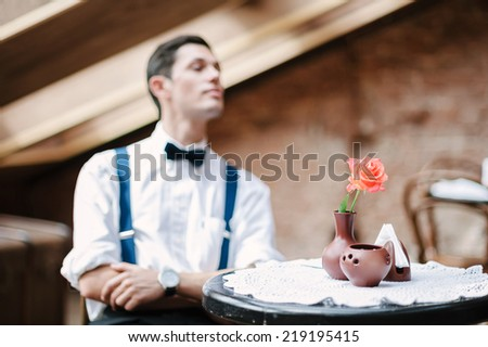 Man poses in cafe with rose on the table. - stock photo