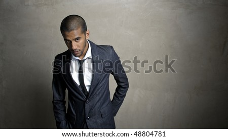 Man poses in his suit in front of grunge wall - stock photo