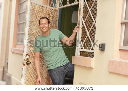 Man posing from the doorway and smiling - stock photo