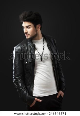 Man posing in black leather jacket, studio shot, dark background - stock photo