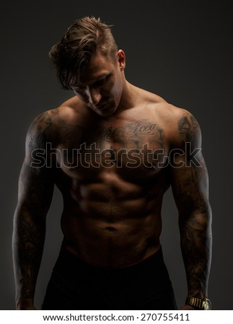 Man posing in deep shadows and looking down. Isolated on grey  - stock photo
