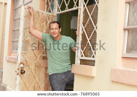 Man posing in the doorway - stock photo