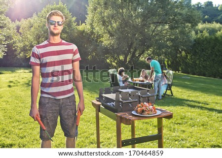 Man, posing next to a barbecue, holding a fork and pliers, with a group of friends sitting around a pick nick table in the background on a sunny summer afternoon.