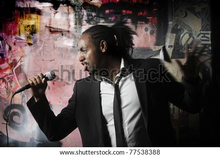 man posing with a microphone by graffiti wall - stock photo