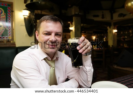Man posing with dark beer mug in a pub - stock photo