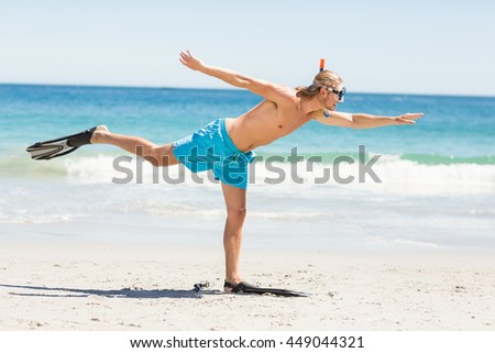 Man posing with diving mask and flippers on beach - stock photo
