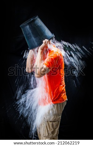 man pour a bucket of ice topped their head on a black background. - stock photo