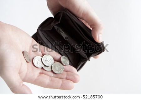 Man pouring coins into empty wallet - stock photo