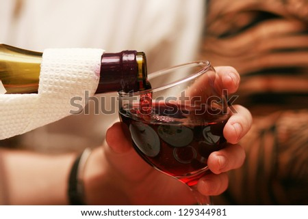 Man pouring red wine into the glass - stock photo