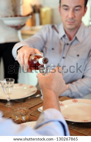 Man pouring wine during meal - stock photo