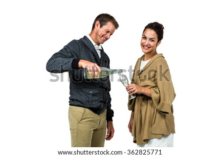 Man pouring wine in glass with woman on while background - stock photo