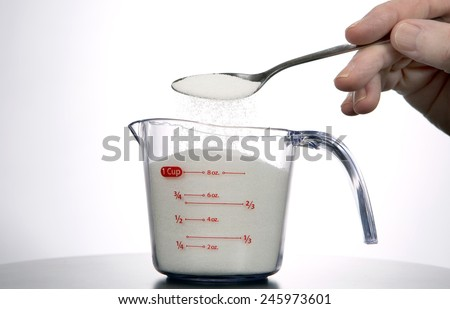 Man pours a spoonful of sugar into a measuring cup. - stock photo