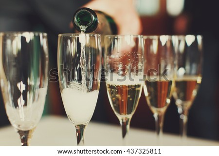 Man pours champagne in wineglasses - stock photo