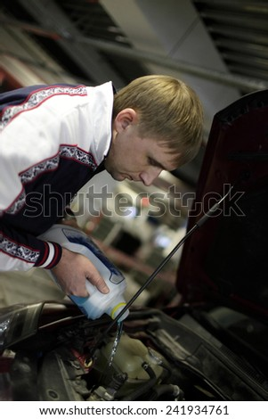Man pours oil into a car in the garage - stock photo