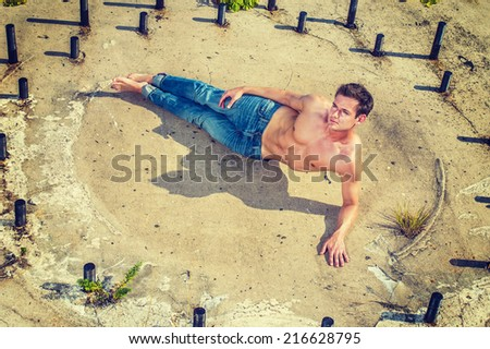 Man Power. Wearing jeans, barefoot, half naked, a muscular guy is lying on the concrete ground within a circle of rusty metal rods, looking up, thinking, symbolic from past to future. - stock photo